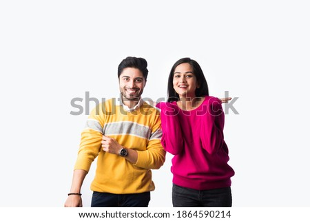 Asian Indian couple wears colourful warm sweater or woolen winter cloths, standing isolated against white background Stock photo ©