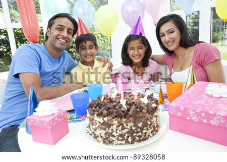 Asian Indian family, mother, father, son & daughter celebrating a birthday party with a chocolate cake