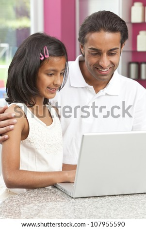 Asian Indian father and daughter, man and girl, using laptop computer in the kitchen at home