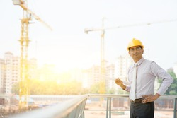 Asian Indian male site contractor engineer with hard hat holding blue print paper at construction site, crane with golden sunlight at the background.