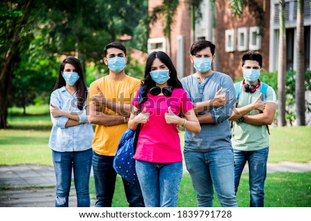 Asian Indian students wears face mask and follow social distancing norms in college or university campus after corona Pandemic unlock, focus on one student Photo stock ©