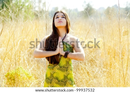 Asian indian woman praying hands  in golden field with green dress