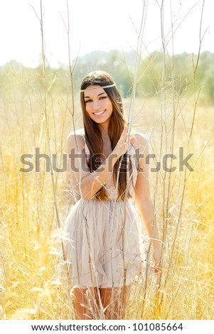 Asian indian woman walking in golden dried grass field