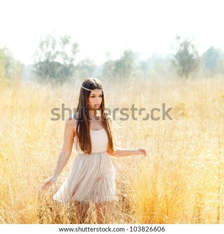 Asian indian woman walking in golden dried grass field - stock photo