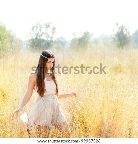Asian indian woman walking in golden dried grass field