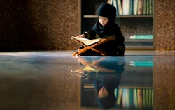 Asian Indonesian Muslim kid is reading the Quran. The Quran is indicated as the guided book for all Muslim and it is direction  to be on the heaven of God.Mosque,Islam,religion and knowledge concept.