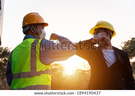 Asian industry construction site worker and foreman wearing hygiene face mask elbow bump greeting adaptation to prevent Coronavirus or Covid-19 spreading at warehouse near the sunset, New Normal Photo stock ©