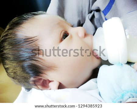 Asian​ infant​ baby boy eating​ and mother give suckling​ breast feed​ing bott milk . Concet bonding​ and attackment