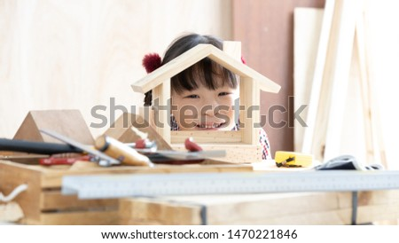 Asian kid girl carpenter working on woodworking table in home carpentry shop, Little asian kid girl works in home carpentry shop. #1470221846