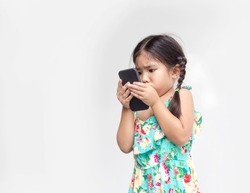 asian kid girl move mobile close face to watch video clip on isolate background in addict digital life style concept