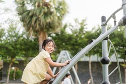 Asian kid girl playing on a swing and having fun in park.Little asian girl climbing rope at playground.Asian child girl playing on playground in outdoor park.Happy Little asian girl outdoor play park.