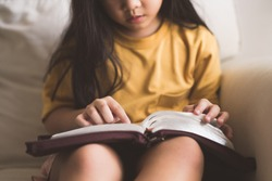 Asian kid girl read bible study.Worship at home.Sunday school.Bible on kid hands.Family christian ,Reading bible study.Hands holding on a Holy Bible.faith, spirituality and religion.child Pray online.
