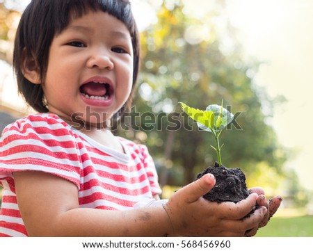 Asian kid hand holding young tree for planting over sunlight and green nature environment - stock photo