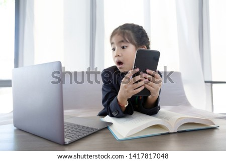 asian kid in business use laptop and mobile as hard working and confidence face in digital generation .Digital generation communicate with online in internet of thing.