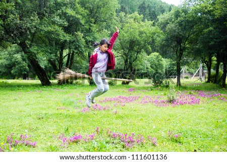 Asian kid jumping on the meadow  in rural area of Shangri-La county,Yunnan province, China