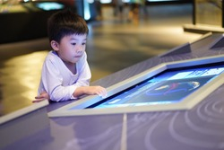 ASIAN KID LEARNING FROM INTERACTIVE TOUCHSCREEN DISPLAY