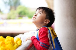 ASIAN KID LOOKING UP FEELING WORRIED ABOUT SOMETHING