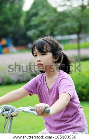 Asian kid riding bike in the park at sunset