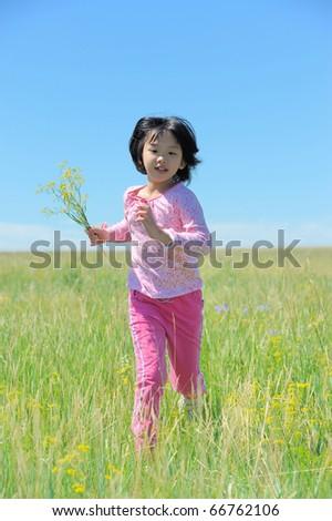 Asian kid running on the grassland