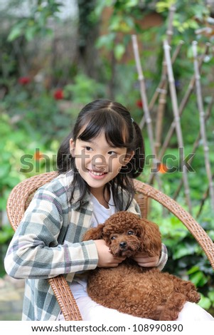Asian kid sitting and holding poodle dog