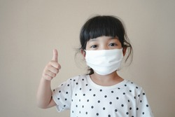 Asian kid use medical mask or surgical mask to protect her from virus, sickness, Covit-19 and coronavirus infection.