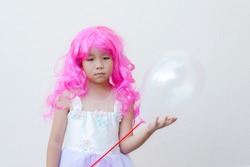 Asian kid wears a pink wig,a fancy dress and hold a white balloon.