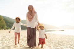 Asian kids having leisure time with their mother at the beach.