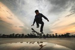 Asian Kids Jumping Tricks - ollie while Skateboarding on-street parking during sunset time., Backlight dark Skateboarder silhouettes
