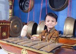 Asian kids playing the Gamelan with batik clothes. Gamelan is a musical instrument typical of Indonesia, Central Java