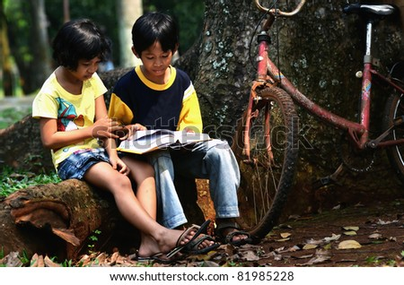 Asian kids studying in the park after school - stock photo