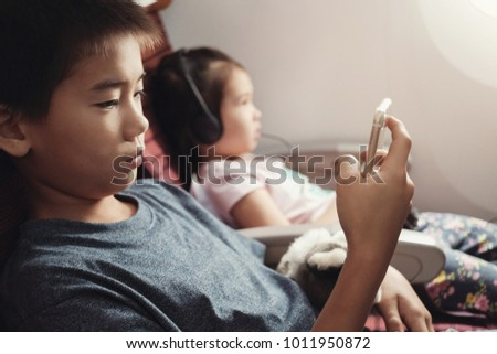 Asian kids using smart phone in flight, family traveling abroad with children