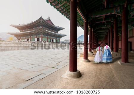 Asian Korean woman dressed Hanbok in traditional dress walking in Gyeongbokgung Palace in Seoul, South Korea.\r