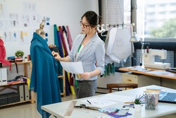 asian korean woman tailor in seamstress workshop working. stylish female fashion designer with measuring tape on neck looking at mannequin and sketch paper in studio. girl staff checking with draw