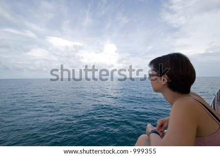 Asian lady aboard a dive boat, looking out into the open ocean