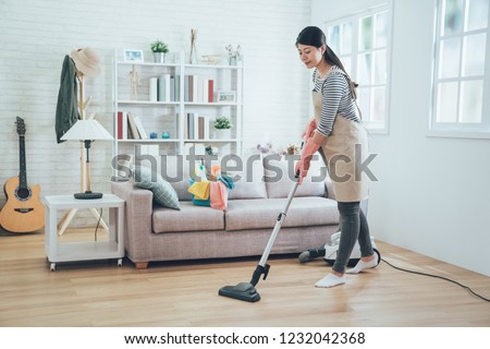 asian lady doing house chores in apron. young housewife using vacuum cleaner cleaning the wooden floor in the living room. happy housekeeper doing housework at home with attractive smile on face. #1232042368