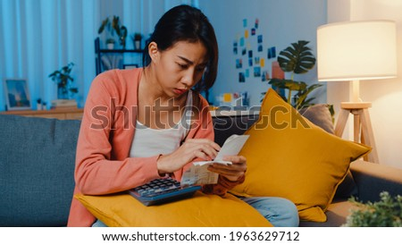 Asian lady feel stress and worried with bill and invoice credit card calculating loan on sofa at home. Home loan stress, Get loan no job,  Coronavirus hardship loans, Can't make loan payment concept.