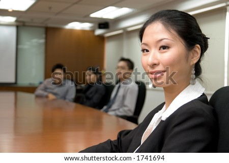 Asian lady in business attire in front of conference room