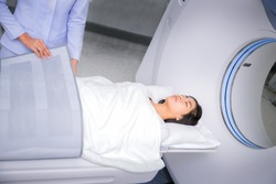 Asian lady sleep on a CT Scan bed and panel control by Radiologic technician