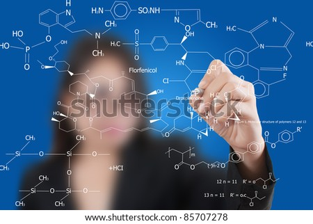 Asian lady teacher writing science diagram.