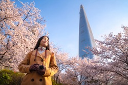 Asian lady travel and warking in cherry blossom park in Seoul city with Sakura flower and tower background, Seoul, Korea, Asia, this image can use for photographer, tourism and holiday concept