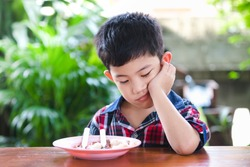 Asian little boy boring eating with rice food on the wooden table, kid without a feeling of appetite