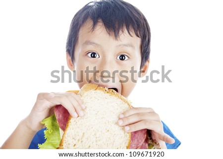 Asian little boy eating big sandwich. shot in studio isolated on white