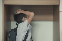 Asian little boy in uniform sitting under the table with panicky when the earthquake at the school with concept