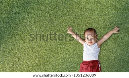 Asian little boy smile and lay on grass  background #1351236089