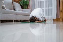 Asian little boy wearing Koko shirt dress prostrate pray on the prayer mat