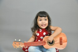 Asian little child girl playing guitar or ukulele isolated on gray background. Music,musician and guitarist concept