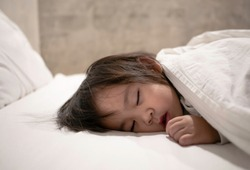 Asian little child girl sleeping in the bed comfortable. Health care concept.