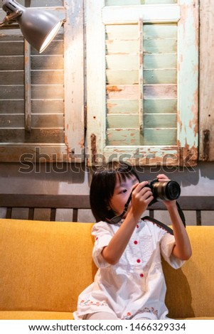 Asian Little Chinese Girl playing camera at an indoor cafe