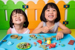 Asian Little Chinese Girls Playing with Colorful Clay in Indoor Playground