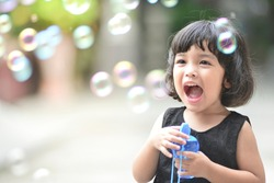 Asian little cute girl or kid blow,play air soap bubbles with smile. happiness,fun and childhood concept .